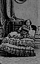 Eugénie leaning while seated wearing a crinoline dress