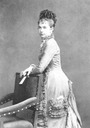 Gisela standing in mid 1870s day dress